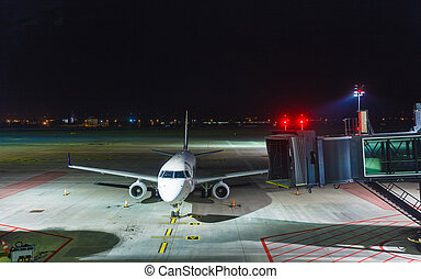 White passenger jet plane on runway at night