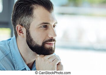 Handsome bearded man resting his chin on folded hands - Full...