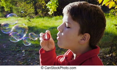 boy blowing up the soap bubbles in autumn forest