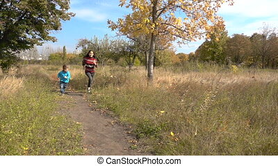 Two kids running together on autumn park