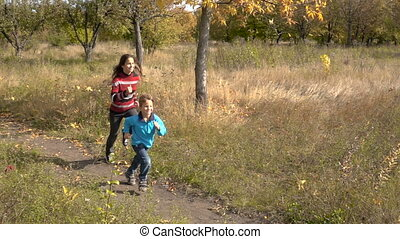 Two children running together on autumn park