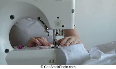 Woman sewing a white sheet