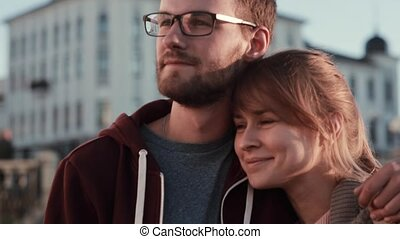 Portrait of young beautiful couple standing in the city...