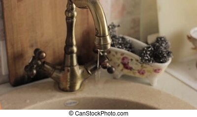 Old copper kitchen faucet with running water drips.