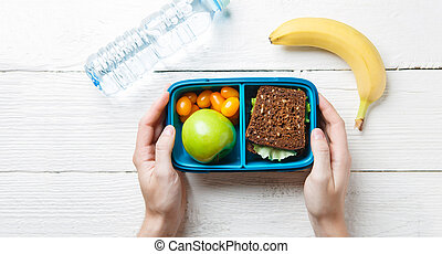 Picture of man's hands with useful lunch in box, bottle of...