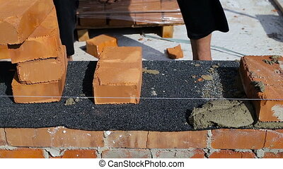 Work lays bricks on a construction site on open air.