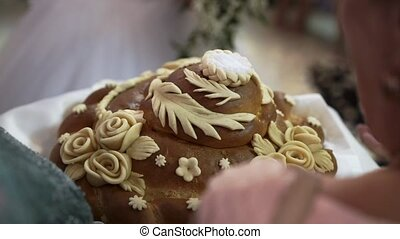 Newlyweds breaking traditional wedding bread at celebration