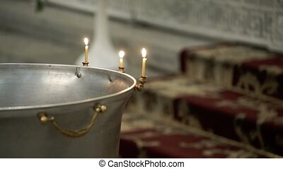 Baptismal font in church with candles