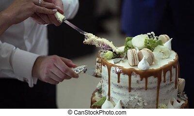 Cutting piece of wedding cake slowmotion