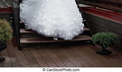 Bride walking on terrace at rainy weather - Unrecognizable...