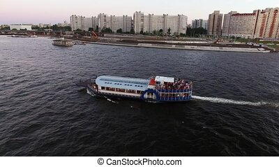 Passenger ship in a city river at the evening