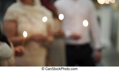 People with candles in church blur