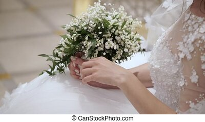 Bride sitting with bouquet indoors