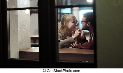 View through the window. Happy young couple spending time in the cafe in the evening, kissing sitting at the table.