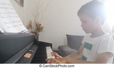 Little boy playing piano against light dust