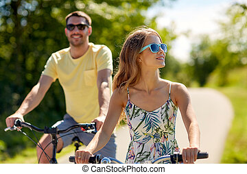 happy young couple riding bicycles in summer
