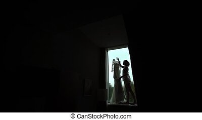 Young woman with wedding dress silhouette near window