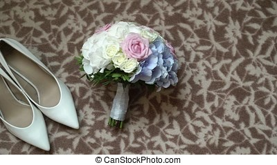 Woman's shoes on heels and bouquet on the floor