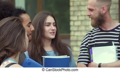 Close up view of students talking in front of university....