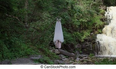 Wedding dress near waterfall at nature