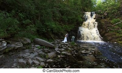 Young wedding couple walking near waterfall in forest