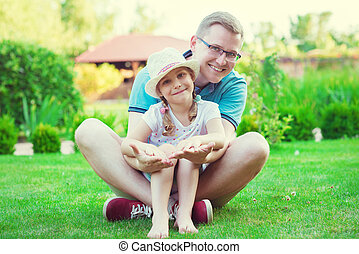 Portrait of happy young father with his pretty little...