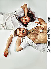 Portrait of two relaxing doctors laying on the floor -...