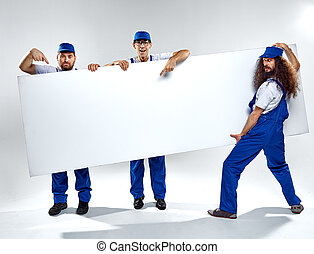 Conceptual picture of three crafstmen holding an empty board...