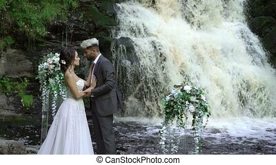 Young wedding couple at ceremony near waterfall - Young...
