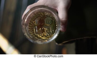 Man holding glass of whisky with ice closeup