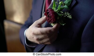 Groom put on boutonniere closeup
