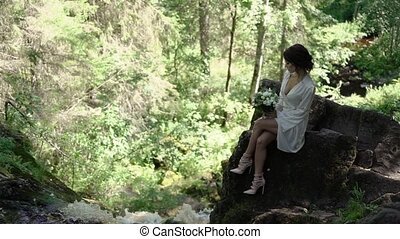 Young woman sitting on a rock near waterfall in lingerie