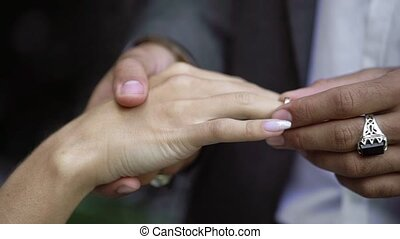 Young wedding couple exchange rings at ceremony near...