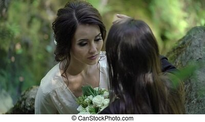 Young woman doing makeup in a forest