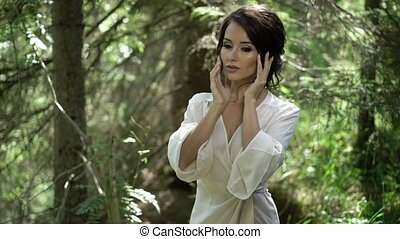 Young woman touching herself in forest in lingerie