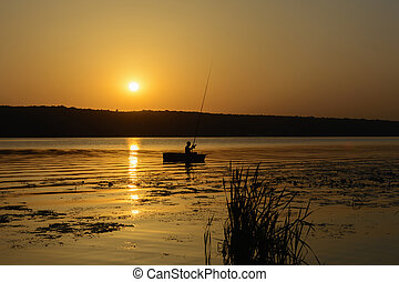 Silhouette of a fisherman in a boat with a fishing rod on...