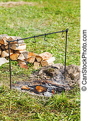 Fireplace with coals and holder for cauldron. Camping in...