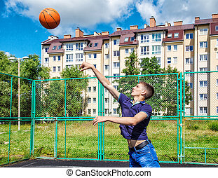 young man training in basketball on sunny summer day closeup