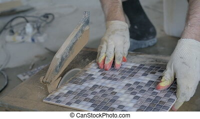 Master gloves cuts ceramic tiles on a special torch on the...