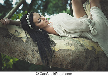 pretty young  woman in romantic dress lie on tree in park