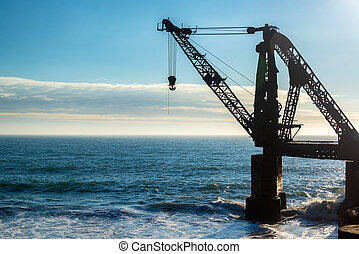 Old Crane and the Sea - Silhouette of an old abandoned crane...