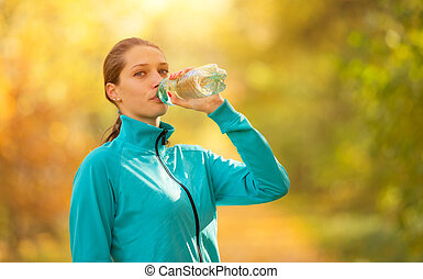Young woman drinking fresh water during her fitness exercise...
