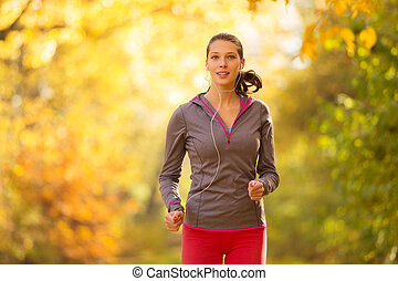 Young brunette woman running in autumn forest listening to...