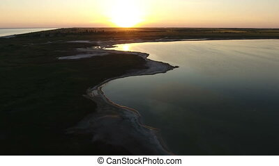 Aerial shot of a beautiful sunset over a long island on a shelf of the Black Sea