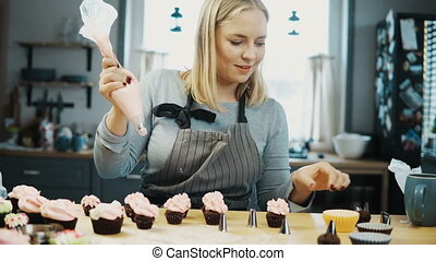 Young beautiful woman decorating the little cupcakes with...