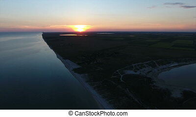 Aerial shot of a  big orange sun at sunset over an island in the Black Sea