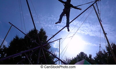 Silhouette of boy jumping on bungee trampoline - Silhouette...