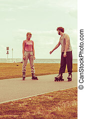 Couple wearing rollerskates looking at each other - Active...