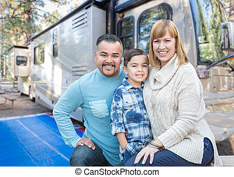 Happy Young Mixed Race Family In Front of Their Beautiful RV At The Campground.