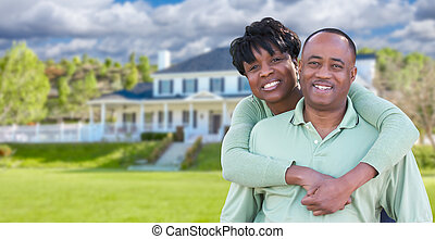 Happy African American Couple In Front of Beautiful House.